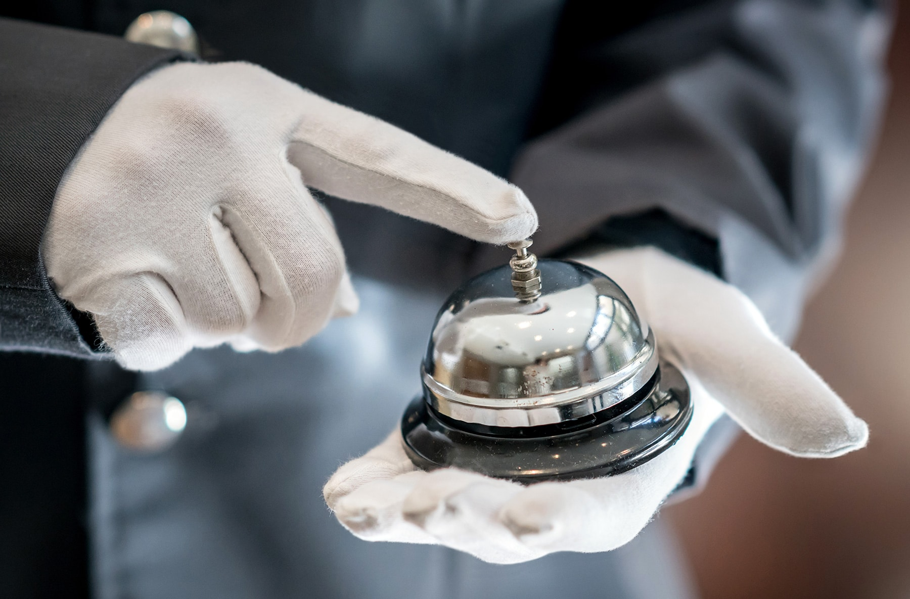 NFCW Expo's concierge service. Picture of white gloved hands holding a hotel bell.